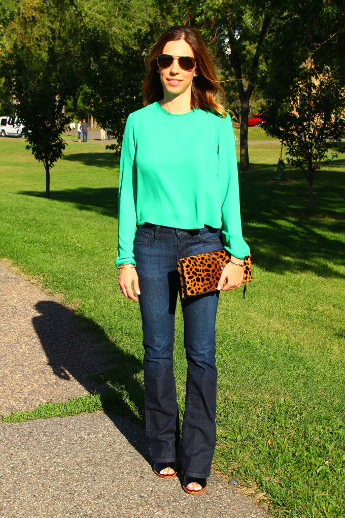 Green crop, flared denim jeans and leopard clutch